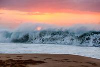 A powerful wave breaks under an orange sunset at Ke Iki Beach, North Shore, O'ahu.