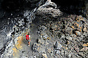ID00209-00...IDAHO - Hiker walking through Indian Tunnel in Craters Of The Moon National Monument. (MR# S1)