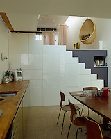 Understairs cupboards provide an expanse of storage and house a cloakroom in this kitchen/dining room