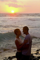 A couple embraces on Hano beach in Kona with a glowing sunset and waves breaking behind them.
