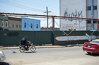 A man on a motorbike in the Bushwick neighborhood of Brooklyn in New York on Saturday, April 27, 2013. The neighborhood is undergoing gentrification changing from a rough and tumble mix of Hispanic and industrial to a haven for hipsters, forcing many of the long-time residents out because of rising rents.  (©Frances M. Roberts)
