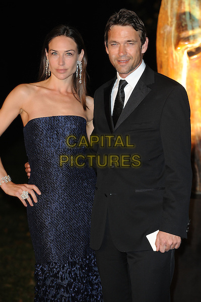 Claire Forlani and Dougray Scott.Raisa Gorbachev Foundation party Stud House, Hampton Court Palace, East Molesey, Surrey, England..22nd September 2011.half length blue navy strapless dress black suit hand on hip married husband wife.CAP/WIZ.© Wizard/Capital Pictures.