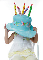 20 July 2008: Two year old young girl Meagan Jennings (2) wears a large oversized happy birthday hat while sitting in a chair during a studio shoot against a white background.