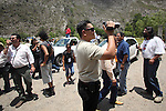 Activists stand up while a military dressed as civilian grabs video as state policemen block the Humanitarian caravan to San Juan Copala on the highway Juxtlahuaca-San Juan Copala, June 08, 2010, as the state authorities try to stop the caravan. More than four hundred people make their way to San Juan Copala's Autonomous Municipality, carrying 35 tons of food to the Triqui people of San Juan Copala sieged by the paramilitaries of the ruling party PRI's Union para el Bienestar Social de la Region Triqui (UBISORT). Photo by Heriberto Rodriguez