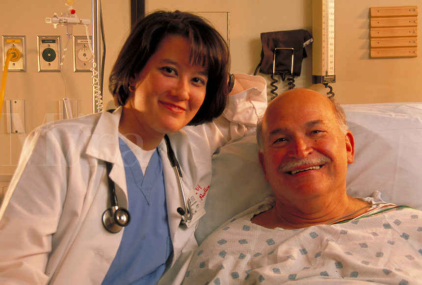 In hospital recovery room a female doctor poses with happy elderly male heart patient. woman doctor and elderly man.