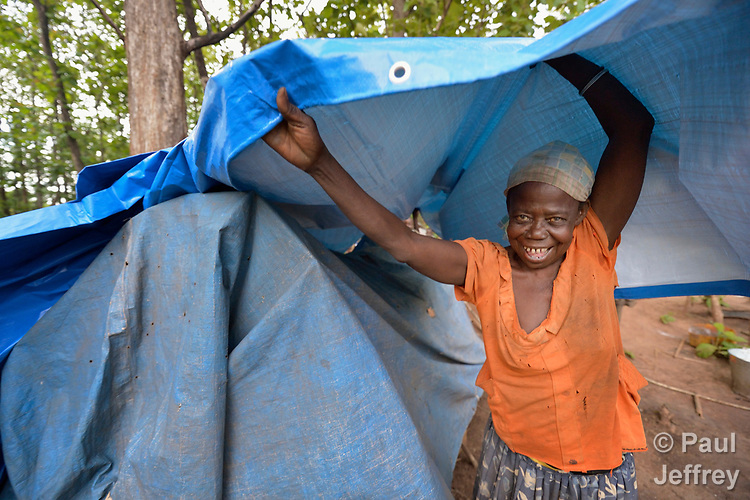 A woman places a new tarp atop her leaky shelter in a camp for for than 5,000 displaced people in Riimenze, in South Sudan's Gbudwe State, what was formerly Western Equatoria. Families here were displaced at the beginning of 2017, as fighting between government soldiers and rebels escalated.<br /> <br /> Two Catholic groups, Caritas Austria and Solidarity with South Sudan, have played key roles in assuring that the displaced families here have food, shelter and water.<br /> The camp formed around the Catholic Church in Riimenze as people fled violence in nearby villages for what they perceived as the safety offered by the church.