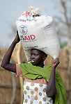 A displaced woman carries home grain on her head in Agok, a town in the contested Abyei region where tens of thousands of people fled in 2011 after an attack by soldiers and militias from the northern Republic of Sudan on most parts of Abyei. Although the 2005 Comprehensive Peace Agreement called for residents of Abyei--which sits on the border between Sudan and South Sudan--to hold a referendum on whether they wanted to align with the north or the newly independent South Sudan, the government in Khartoum and northern-backed Misseriya nomads, excluded from voting as they only live part of the year in Abyei, blocked the vote and attacked the majority Dinka Ngok population. The African Union has proposed a new peace plan, including a referendum to be held in October 2013, but it has been rejected by the Misseriya and Khartoum. The Catholic parish of Abyei, with support from Caritas South Sudan and other international church partners, has maintained its pastoral presence among the displaced and assisted them with food, shelter, and other relief supplies.