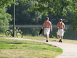 Two men who are dressed the same, walk shirtless around Lake Nokomis in Minneapolis in July