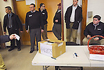 New Gloucester, Maine: February 11, 2012.<br /> <br /> Votes are cast during a caucus of Republicans voting for their party's presidential candidates on the final day of the week long Maine Caucuses. The five men at center and right are observers from the Mitt Romney presidential campaign. Standing at left is a volunteer from the Ron Paul campaign. This caucus happened inside a gymnasium at the Memorial School. Mitt Romney was declared the statewide winner. Ron Paul took second place. The statewide results we called into question by Paul supporters when it was learned that the results of several caucuses were not included in the final tally, and when it was learned that one county cancelled their caucuses due to inclement weather. Paul is running third time for the presidency. Romney is running a second time. &copy;Chris Fitzgerald / CandidatePhotos