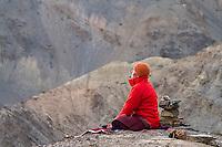Monk in morning meditation. On the old road  ('Jalebi Mod') near Lamayuru Village,  Ladakh, Jammu and Kashmir, India