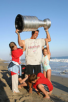 24 August 2002: Detroit Red Wings professional hockey player Chris Chelios holds the NHL Stanley Cup over his head away from his kids Caley, Dean, Jake and Tara on the beach at sunset in front of their summer home in Malibu north Los Angeles. .