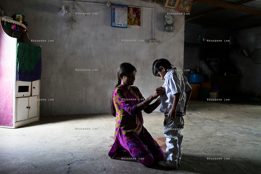 Hemant Jat, 6, gets dressed for school with the help of his sister, Sapna Jat, 18, at home in Maheshwar, Khargone, Madhya Pradesh, India on 13 November 2014. Hemant, the son of a Fairtrade cotton farmer, wants to be a police man when he grows up and gets a 5% discount of school fees at the Vasudha school. His father Nandaram would be happy if Hemant took over the farm but if he does well in school, he could look for other careers. Photo by Suzanne Lee for Fairtrade