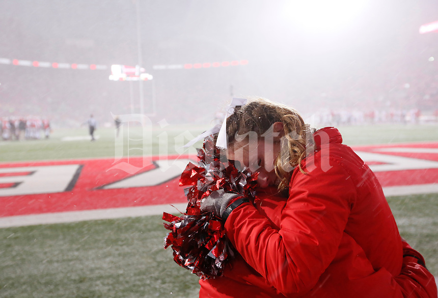 Ohio State Buckeye cheerleader Ally Nelson huddles with Danny Ohler during a snow squall during Ohio State Indiana game at Ohio State Stadium in Columbus  Nov. 23, 2013.