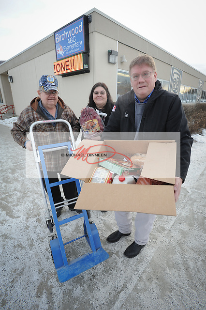 From left, Eagle River Lions Club member Finis Shelden, school nurse Beth Thomas and Chugiak Lions Club member Bill Stoltze show one of the Thanksgiving meals delivered to Birchwood ABC Elementary Monday, November 21, 2016.  Shelden and Stoltze had spent the morning delivering meals to area schools to be distributed for the coming holiday.  Photo for the Star by Michael DInneen