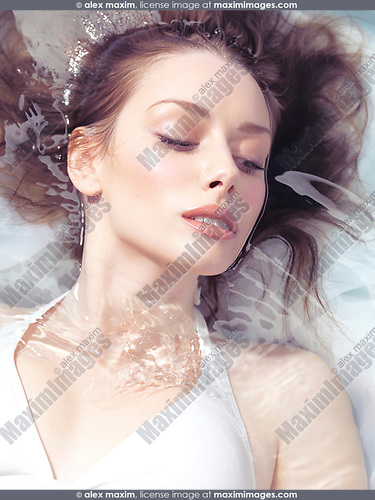 Beauty portrait of a young beautiful woman with natural look makeup lying in shiny clear water, cloesup of face