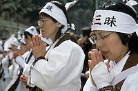 Lay priests pray and chant as Yamabushi or mountain priests walk across the embers of a large bonfire of ceder branches in the Hi Watari, fire walking, festival of Takao san Guchi near Tokyo, Japan. Sunday March 11th 2007