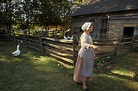 Female reenactor/guide at Landis Valley farm museum Lancaster PA Pennsylvania.  historical collection of late 1800's early 1900's equipment antiques Landis Valley farm museum Lancaster PA Pennsylvania.  historical collection of late 1800's early 1900's equipment antiques