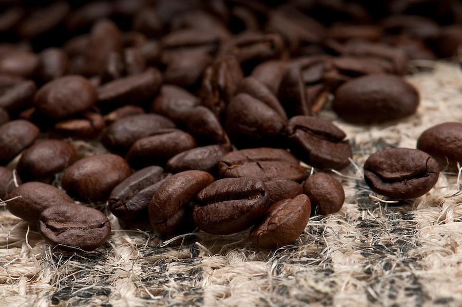 Macro shot of coffee beans over burlap.