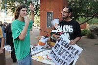 Phoenix, Arizona. September 17, 2012 - A small crowd of demonstrators in Phoenix, Arizona gathered to mark one year since the beginning of the Occupy Movement that opposes Wall Street and large corporations that represent the one percent who control wealth in the United States. In this photograph, Michael Nehl Royeran, an activist with the Occupy Phoenix group uses a megaphone to address participants before the beginning of the march around Downtown Phoenix. To the right is Orlando Arenas, an organizer with the Puente Arizona movement. Photo by Eduardo Barraza © 2012