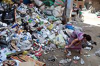 2011 Mokattam Garbage City (alla periferia del Cairo) il quartiere copto dove si vive in mezzo alla spazzatura raccolta: una bambina a piedi nudi raccoglie qualcosa tra l'immondizia accumulata in una strada. Egypt Cairo Garbage city ..Egipte   chiffonniers du Caire