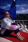 Woman enjoying sun on sailboat moored off Blake Island in Puget Sound Seattle Washington State USA.