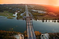 Aerial view of traffic on the Pennybacker 360 bridge and Colorado River near Austin Texas at sunset