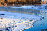 Sunlight skims the surface of ice along the Bitterroot River near Missoula, Montana