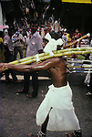 Thaipusam Hindu festival in  the streets of Singapore. Devotees show their faith by enduring piercing and carrying heavy weights attached to them through hooks, metal spears and bolts for many hours.