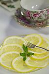 Lemon slices lay on a table with a teacup.