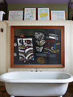 A free-standing bath in the panelled bathroom is dwarfed by a large modern painting