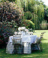The table has been dressed with a checked tablecloth and white textured overcloth and decorated with peonies