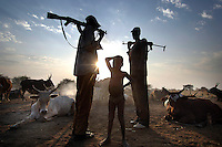 Nuer men armed with Kalashnikovs guarding their cattle against raiders, either bandits or members of hostile tribes, early in the morning. Their owners light small fires fuelled by cow dung in the 'cattle camp', so that the smoke keeps tsetse flies away. After sunrise the young boys will escort the cows to their grazing grounds. Cattle are the most important asset to the nomadic people of southern Sudan.