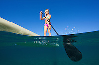 An above and below view of a healthy woman standup paddling at Wailea, Maui.
