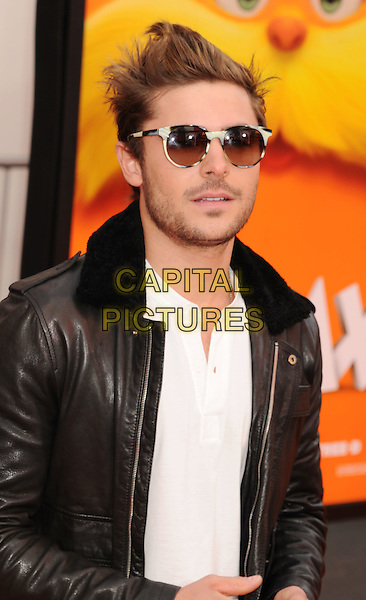 "Zac Efron.arriving at theLos Angeles Premiere of ""Dr. Suess' The Lorax"" Universal Studios Hollywood in Universal City, California, USA,  February 19th, 2012..half length sunglasses black leather jacket  white shirt beard facial hair stubble  .CAP/ROT/TM.©TM/Roth Stock/Capital Pictures"