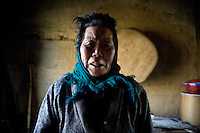 Wang Bao Ying stands in her home in Fanzhuang Village, Gangyun County, Jiangsu, China.  Wang Bao Ying is the grandmother of the orphan boy Fan Lu Yang, 10, whom she cares for with husband Fan Qing Huai.  The grandparents are both over 75 and often ill, and the income from growing corn, wheat, and hay, cannot support the three.  Fan Lu Yang's father died in 2000 in an accident at a small coal mine and his mother developed dementia and disappeared about a year before this picture was taken...At the time of the picture, China's Amity Foundation charity, was investigating the family's situation in preparation to raise money to financially support these children and other orphans in similar situations.  With Amity's support, each orphan, aged 6-12, would receive approximately 1,400 RMB annually (about 200 USD) to pay for the cost of living. Amity works to keep children out of the institutional orphanages in China, preferring to provide monetary assistance that can help maintain a family environment for the orphans it helps.