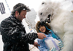 Kamiel Verschuren and Mami Odai (in polar bear outfit) hand out a block of compacted snow to a young passerby during the Sapporo Snow Festival in Sapporo City, northern Japan on 05 Feb. 2010.