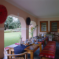 A laid breakfast table is located in the pink-painted loggia creating an open dining room