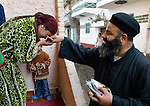 Father Joil Sobhe, a Coptic Orthodox priest, is greeted by a woman as he greets and blesses church members in the Egyptian village of Sakra.