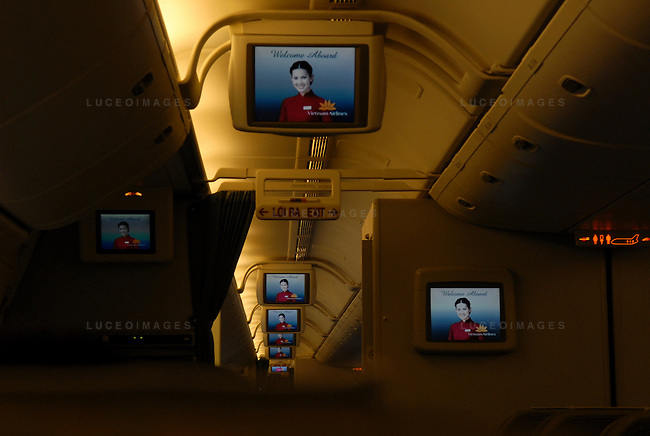 Televisions show a greeting from Vietnam Airlines aboard a plane heading from Hanoi to Ho Chi Minh City, Vietnam.