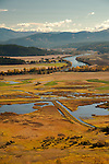 Idaho, Bonners Ferry.  Kootenai River flowing through the Kootenai Valley with the wetlands of Kootenai National Wildlife Refuge in the foerground and the Cabinet mountains in the background in the fall in Idaho