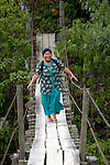 The Rev. Erlincy Rodriguez, a United Methodist pastor, crosses the Agusan River near Tandawan in Mindanao, Philippines, as she visits rural communities as part of her pastoral work.