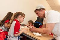 ASDA Newark baker Mark Smith shows gRainbow Lacey Goy, 6, how to knead dough