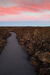 A narrow pathway vanishes into the sunset at Craters of the Moon National Preserve.