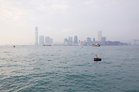 The Tsim Sha Tsui/Kowloon waterfront, dominated by a yet to be completed International Commerce Centre (484m), seen across Victoria Harbour through smog from Hong Kong island