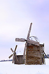 Two ancient log windmills in a snow covered field One big and one small Parent and a child metaphor Ukraine Eastern Europe Countryside winter scenic Vertical orientation