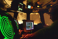 """Assistant skipper Jeff Morehouse guides the fishing vessel """"Polar Lady"""" through a stormy night using GPS, radar, sideband radio, depth finders, and other electronic equipment in the wheelhouse during an opilio crab season in the Bering Sea in January 1995. Nights are long and cold in the arctic in the winter.  Crab fishing in the Bering Sea is considered to be one of the most dangerous jobs in the world.  This fishery is managed by the Alaska Department of Fish and Game and is a sustainable fishery.  The Discovery Channel produced a TV series called """"The Deadliest Catch"""" which popularized this fishery. Today this fishery, largely based out of Dutch Harbor, AK has been consolidated resulting in a lot less boats fishing."""