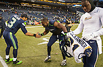 Seattle Seahawks quarterback Russell Wilson (3) and running back Robert Turbin, center, celebrate as  St. Louis Rams safety Maurice Alexander (31) removes his jersey from his shoulder apds at CenturyLink iield in Seattle, Washington on December 28, 2014.  The Seahawks officially wrapped up the No. 1 seed in the NFC playoffs shortly after beating the Rams, 20-6. Despite the Cowboys and Packers also winning to finish 12-4, the Seahawks (12-4) won the multi-team tiebreaker and earned home-field advantage throughout the playoffs for the second consecutive season.  ©2014. Jim Bryant Photo. All Rights Reserved.