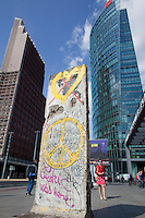 A remaining fragment of the Berlin Wall in Potsdamer Platz. In the background is the Sony Centre, the Deutsche Bahn HQ, and the entrance to the Potsdamer Platz U-Bahn station which was a &quot;ghost station&quot; through which trains passed but could not stop during the years of the Wall and the Cold War.