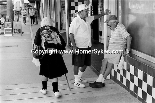 Two old men passing the time of day chatting while an old woman walks past using a walking stick South Beach Miami Florida. .