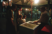 Visitors to the nightly street market in Tashkent, host to people selling arts, crafts, belongings, and to various eateries. Uzbekistan.